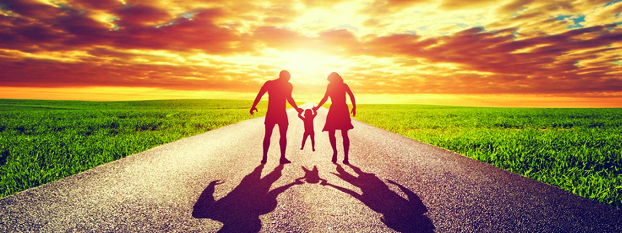 Man, woman and young child walking towards the sunset.